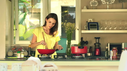 Young, pretty woman cooking and adding seasoning in kitchen