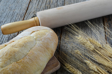 Fresh Bread with a Rolling Pin and Wheat on a Rustic Wood Table