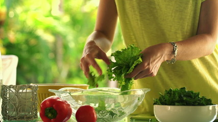 Woman hands picking salad leaves into glass bowl in kitchen