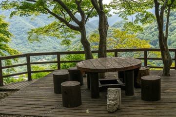Small picnic table and benches on top of a mountain.