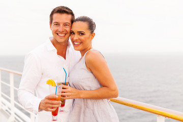 young married couple having cocktail on cruise