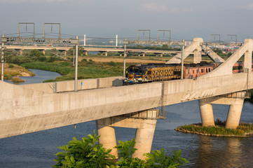 Korean locomotive on a concrete bridge over a river.