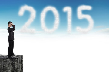 business man looks through on cloud in blue sky number 2015