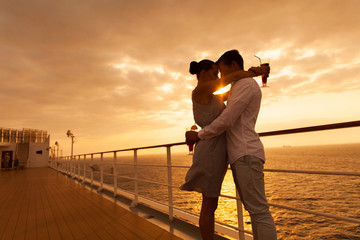 couple hugging with eyes closed at sunset on cruise