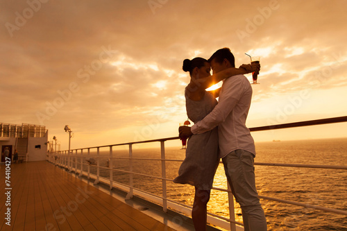 couple hugging with eyes closed at sunset on cruise - 74410427