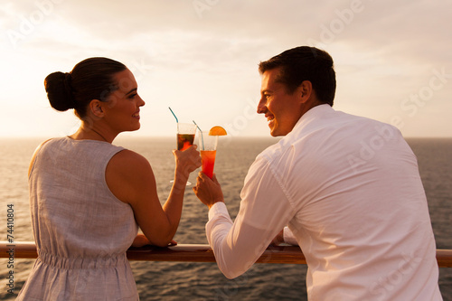 young couple toasting with cocktail on cruise - 74410804
