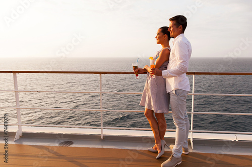 side view of couple having cocktails on cruise ship - 74411079