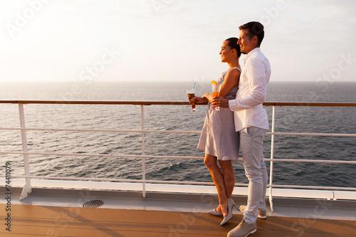 Leinwandbild Motiv side view of couple having cocktails on cruise ship