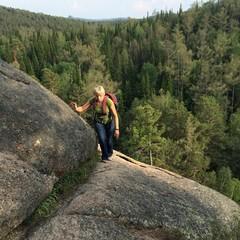 Молодая девушка с рюкзаком на скалах