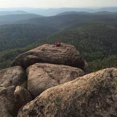 Рюкзак и ботинки на лежащие на скале на фоне гор