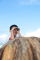 Happy little boy exploring outdoors clambering on a rock with te