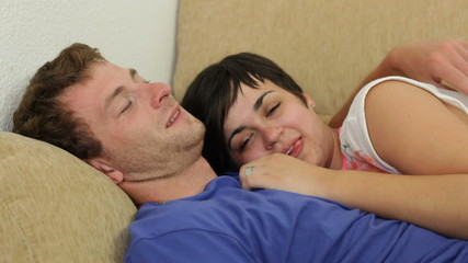 Funny couple in love relaxing on the sofa at home.
