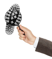 Magnifying glass in hand and shoe printout
