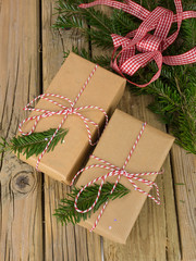 string and brown paper parcels with conifer decoration and ribbo