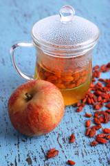 Goji berries drink in glass cup and ripe apple