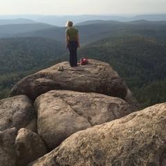 Молодая девушка спортсменка с рюкзаком на скале на фоне гор