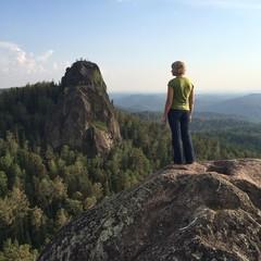 молодая девушка на вершине скалы на фоне гор
