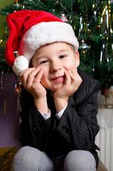 kleiner Junge wartet unterm Christbaum