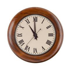 Vintage clockface showing eleven o'clock in wooden frame