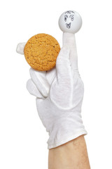 Smiling finger puppet holds oatmeal cookie