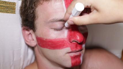 Closeup of a man face painting flag of England.