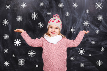 A girl stands on the background of of falling snowflakes