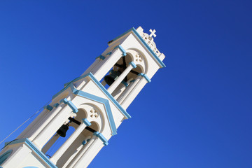 Tall tiered blue and white bell tower on Greek island
