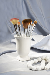 Set of silver cosmetic brushes in the white vase