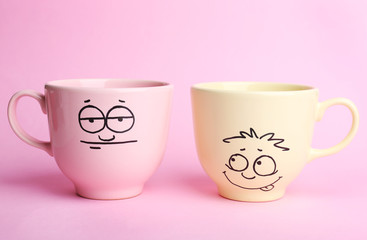 Emotional cups on pink background