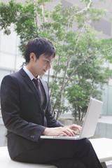 ベンチに座ってパソコンを見るビジネスマン