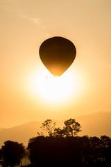Balloons flying past the sunrise