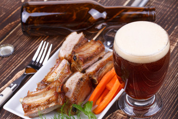 Glass and bottle of beer. Grilled pork ribs and fresh carrot