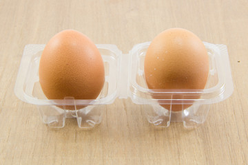 Two raw eggs in plastic box on wood board