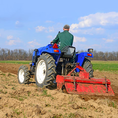 Farmer on tractor handles field
