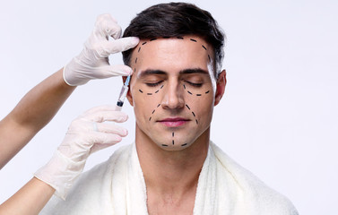 Man with closed eyes at plastic surgery with syringe in his face