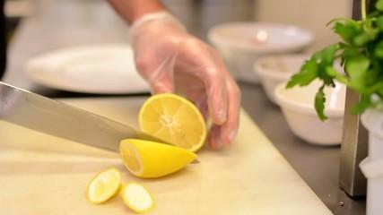 Chef slices lemon in restaurant kitchen