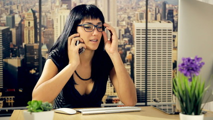 Business woman on the phone in office while working with pc