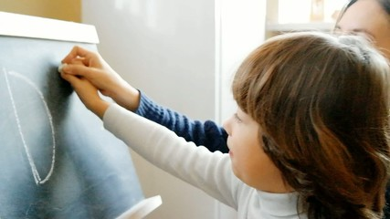 boy with his mother studying letters on a blackboard