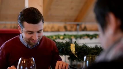 happy couple in restaurant - man eats food - closeup