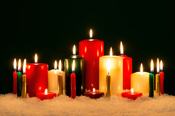 Christmas candles against black background.