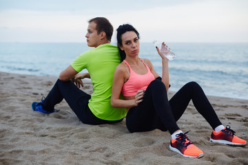 Young fit couple having break after workout outdoors