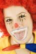 Clown in Kostüm steckt Zunge heraus