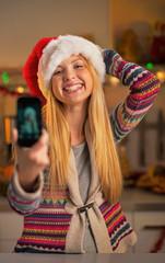 Happy teenager girl in santa hat making selfie