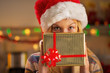 Portrait of girl in santa hat hiding behind present box