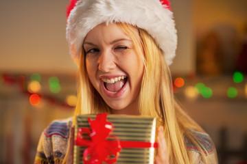 Portrait of girl in santa hat holding christmas present box
