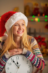 Portrait of smiling teenager girl in santa hat with clock