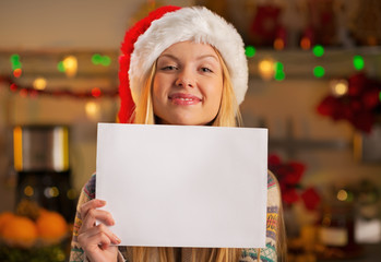 Happy teenager girl in santa hat showing blank paper sheet