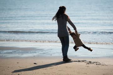 冬の砂浜で遊ぶ親子のシルエット