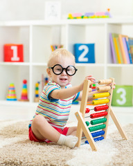 child with eyeglasses playing abacus