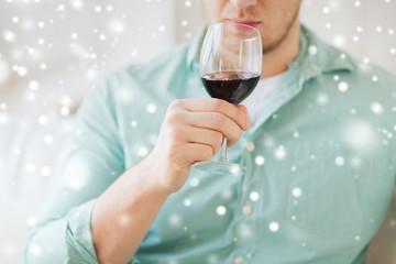 close up of man drinking red wine at home